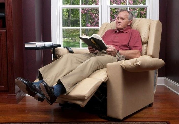 Elder man reading a book while sitting in a tan lift chair recliner.