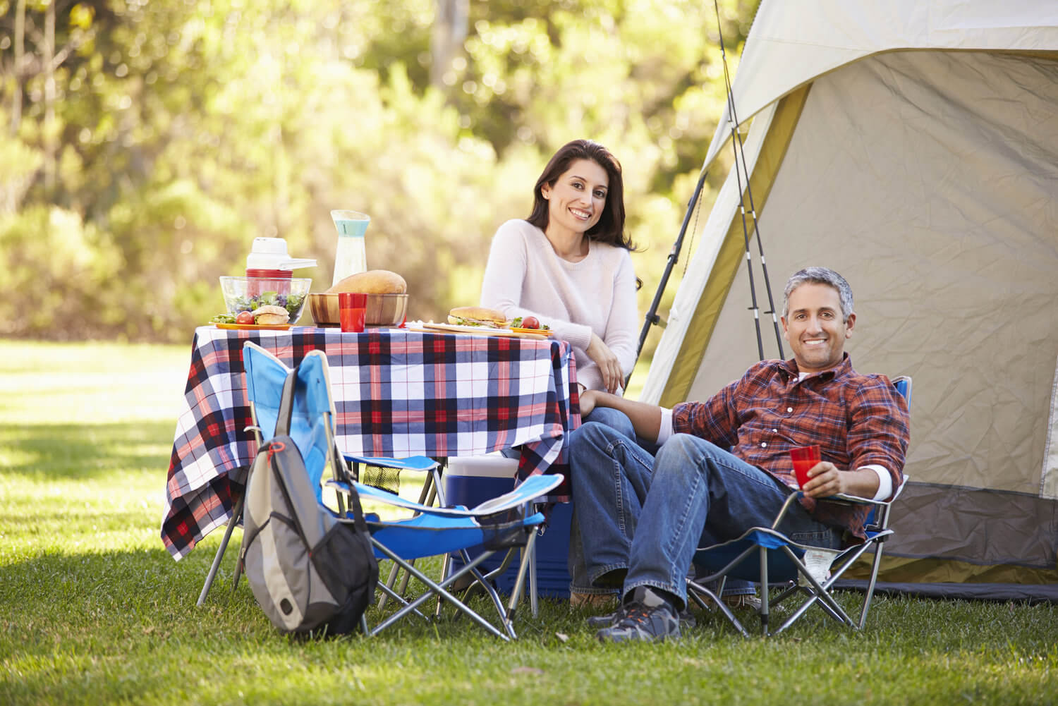 man and woman sitting close together at a campsite during a sunny afternoon