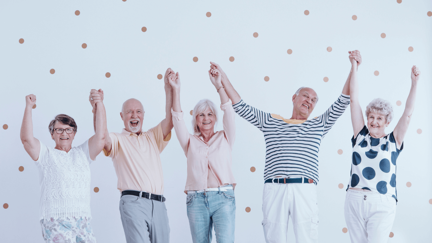 happy senior citizens celebrating with arms raised in the air
