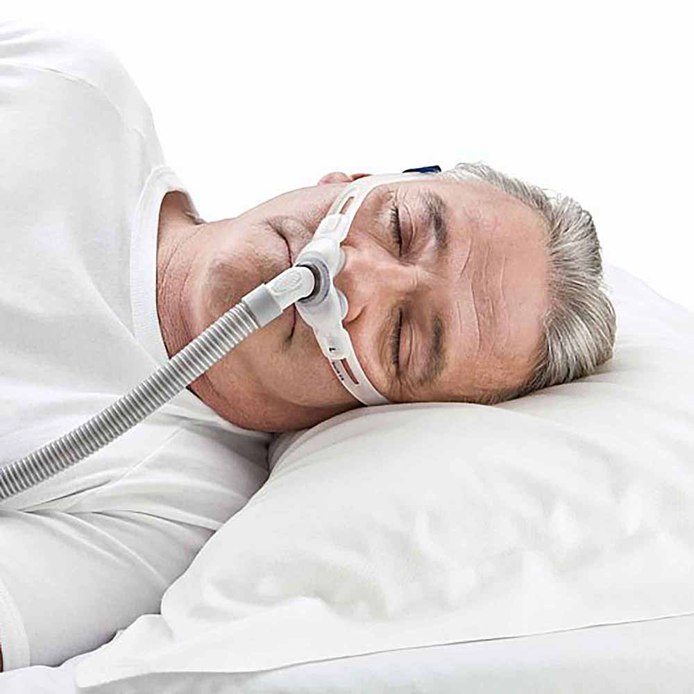 man sleeping on his side wearing a cpap mask
