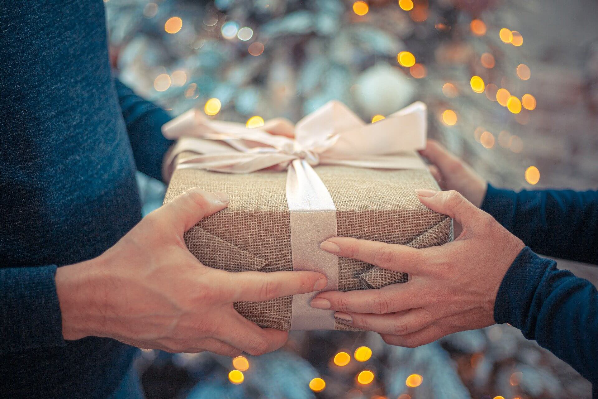 man and woman hands holding wrapped gift with bow