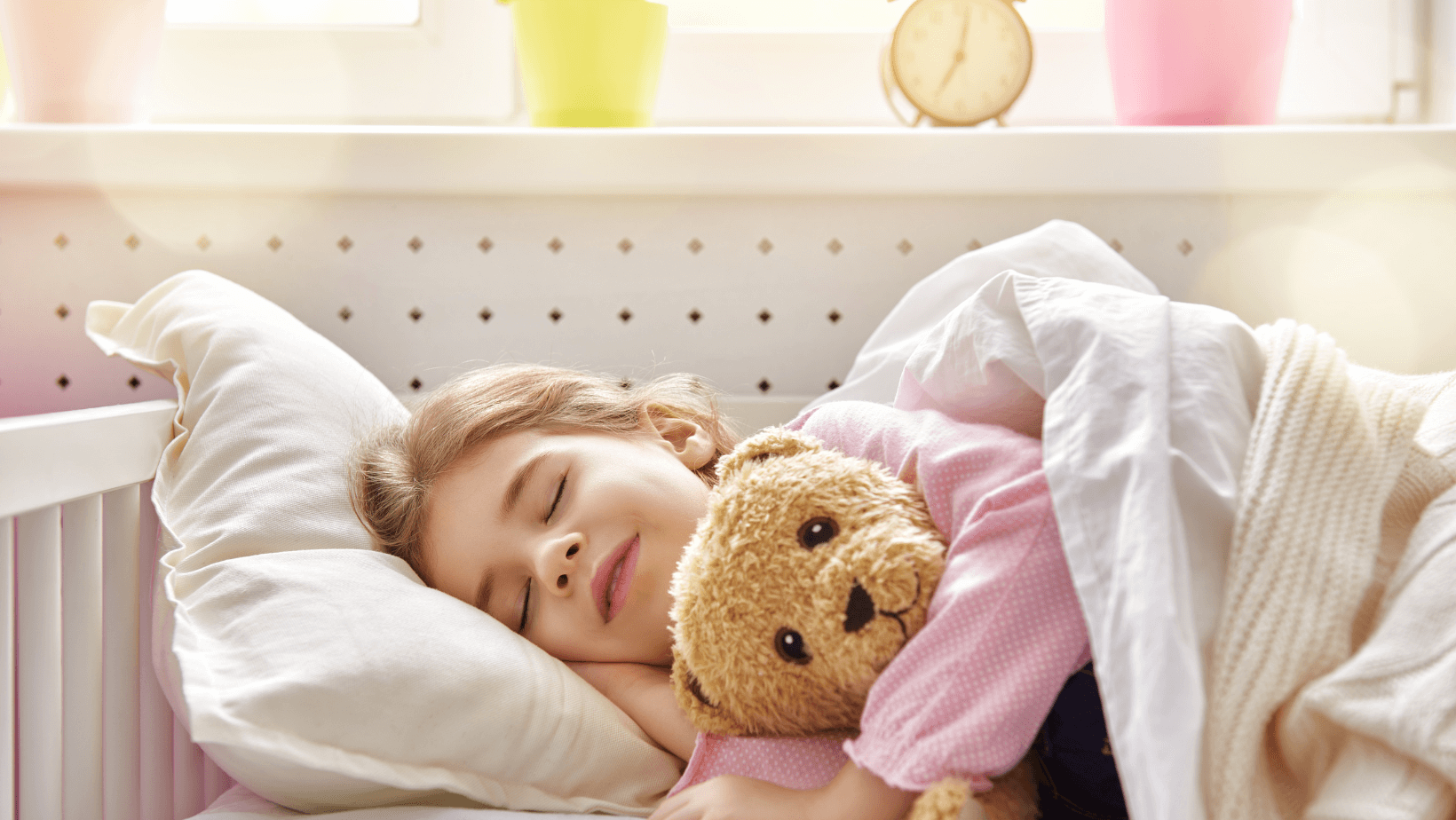 sleeping girl laying in bed holding teddy bear