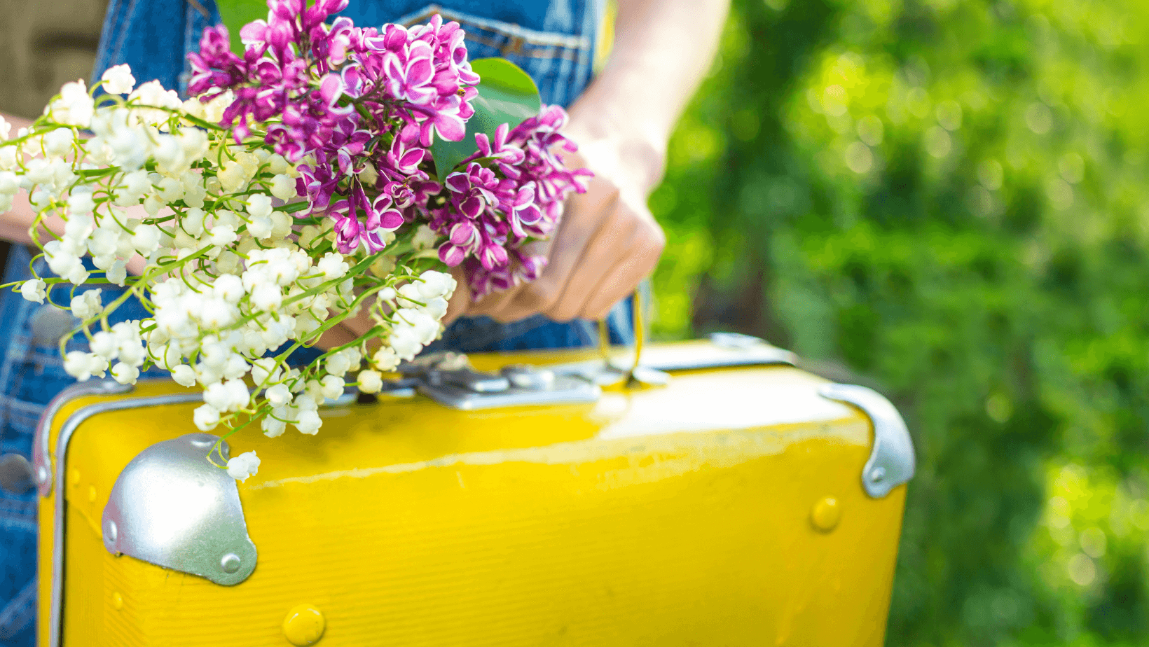 person carrying a yellow suitcase while holding spring flowers