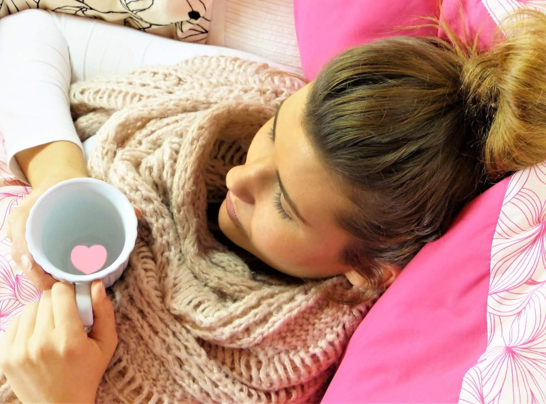 young woman wearing scarf laying down resting with blankets and cup of hot water